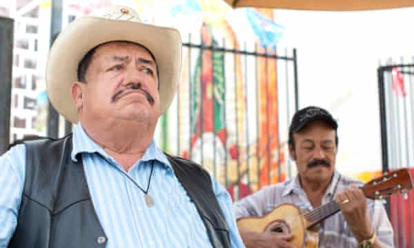 Roberto Olmos sits with his friends playing music in Mariachi Plaza.