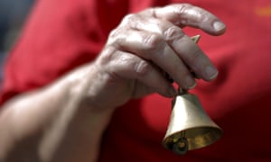 A woman rings a bell outside the church