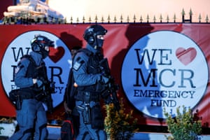 Armed policemen are seen as music fans leave the One Love Manchester concert