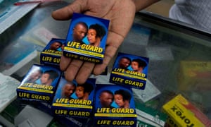 A pharmacist displays a pack of Life Guard condoms at a store in the Ugandan capital Kampala