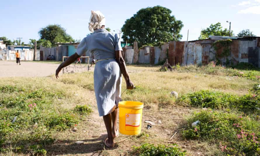 A woman fetches water in Kingston, Jamaica. According to the UN, one in three women in the Caribbean has experienced sexual or physical violence in her lifetime.