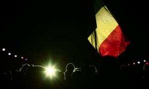 People hold a Belgian national flag in front of the Brandenburg Gate to mourn over the victims of the Brussels attacks in Berlin, Germany