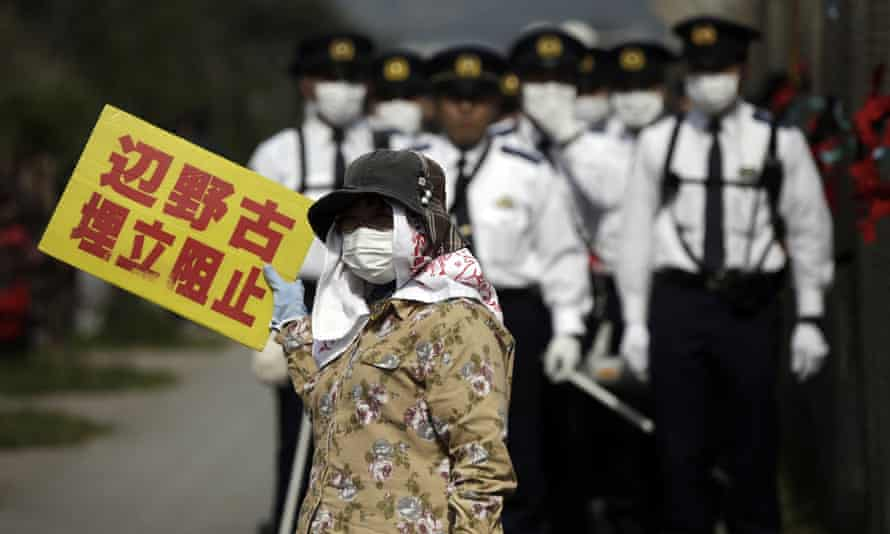 Japanese police officers stand guard in March 2015 during a demonstration against the construction of the Henoko base.