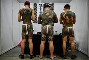 Three tattooed men with backs to camera
