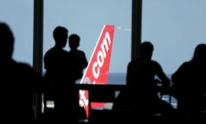People look out at a Jet2.com aircraft from the departures area of an airport.