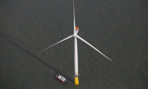 A boat passes a wind turbine in the North Sea at the London Array offshore wind farm