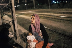 A woman holds her child at a railway station on the Tabanovce border crossing between Macedonia and Serbia. Migrants, among them children and elderly people, are trying to cross Macedonia and Serbia and enter the EU via Hungary. The Hungarian authorities started building a fence along the country's border with Serbia earlier this week to halt the influx.