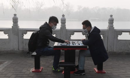 Two men play Chinese chess beside a lake on a heavily polluted day in Beijing on 1 January.