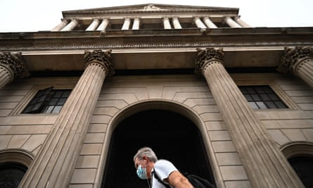 A man in a face mask walking past the Bank of England on Threadneedle Street.