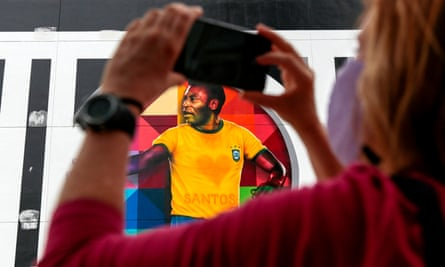 A woman takes pictures of a mural by Brazilian artist Kobra depicting Pelé, in Santos.