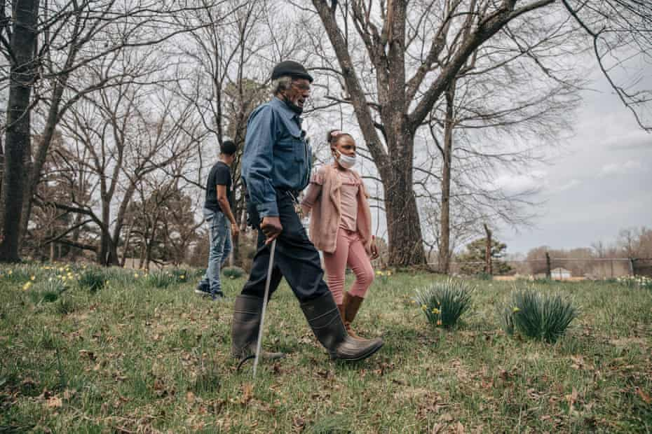 Clyde Robinson and his granddaughter, Aareona Ginns, walk on his land in south-west Memphis.