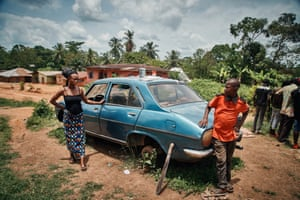 A woman and man next to a derelict car
