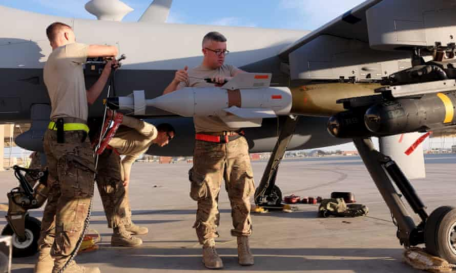 US Air Force ground crew in Kandahar secure weapons to an MQ-9 Reaper drone after its return from a mission.