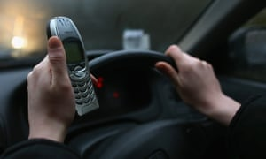 A woman uses her mobile phone while driving