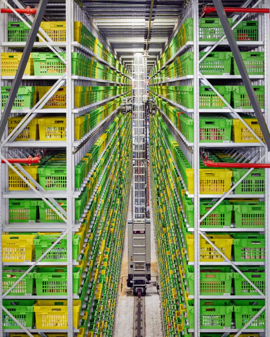 A robotic crane picks crates from towering shelves at an Ocado warehouse in Hatfield