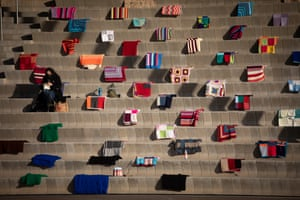 Johannesburg, South Africa. A woman knits a blanket while she sits among other knitted blankets as part of the 67 Blankets for Nelson Mandela Day project. The project, in its 17th year, donates the blankets to those who need them during the cold winter