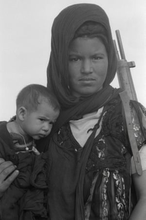 Nouenna, Western Sahara, December 1976. A woman holds her child and a rifle during training of Polisario soldiers in Western Sahara. The Polisario was an army dedicated to fighting Moroccan and Mauritanian occupation