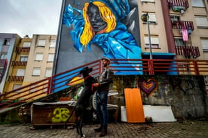 Portuguese artist Acer poses with his dog in front of his mural