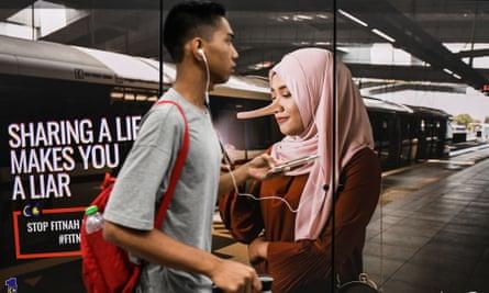 A commuter walks past an advertisement ti discourage 'fake news' in Kuala Lumpur, Malaysia.