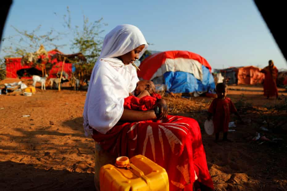 Zeinab, 14, sits as she holds her nephew at a camp for internally displaced people from drought-hit areas in Dollow, Somalia
