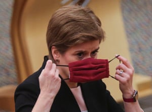 Scotland's first minister Nicola Sturgeon adjusts her face mask during updates to MSPs on any changes to the Covid-19 restrictions at the Scottish Parliament.