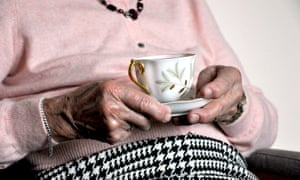 An elderly woman holding a cup and saucer