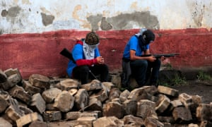 Pro-government supporters sit in a barricade after clashes with demonstrators in Monimbó, Masaya