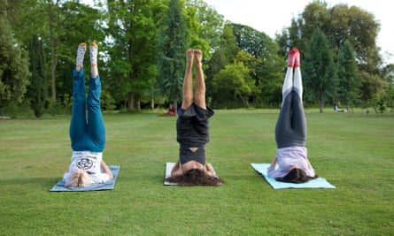 Three guests at Beeja Meditation Retreat, Sussex, try yoga in the grounds.