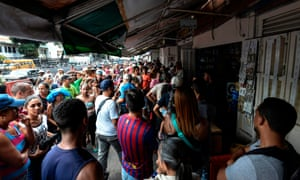 People queue to buy food at Petare neighborhood in Caracas on Sunday during a massive power outage.