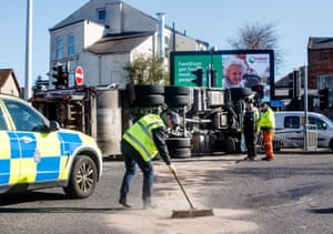 A man in the foreground sweeps sand over oil that has spilt over the road; the bottom of the bin lorry rises behind him