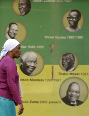 Woman walks past poster with faces of previous ANC leaders