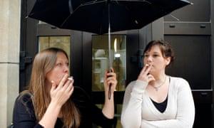 two women smoking under an umbrella