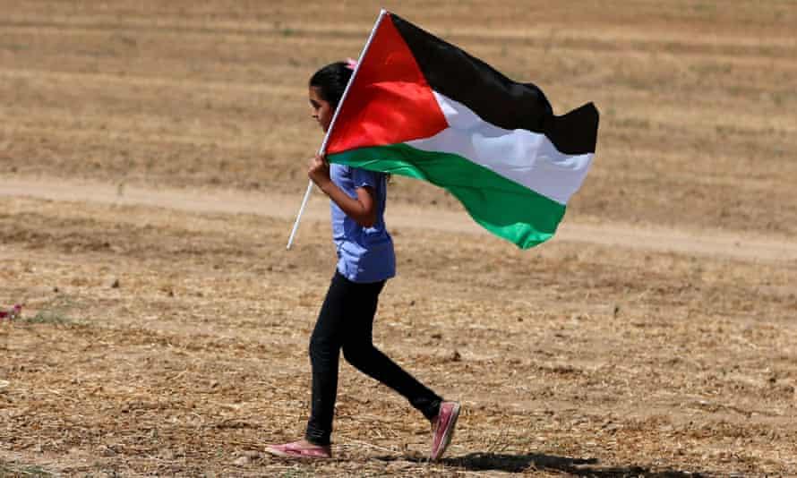An Arab-Israeli girl holds a Palestinian flag.