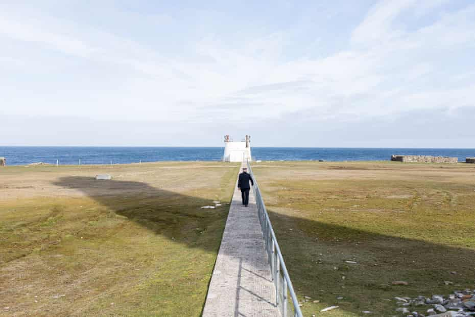 Billy Muir walking in the shadow of the North Ronaldsay lighthouse