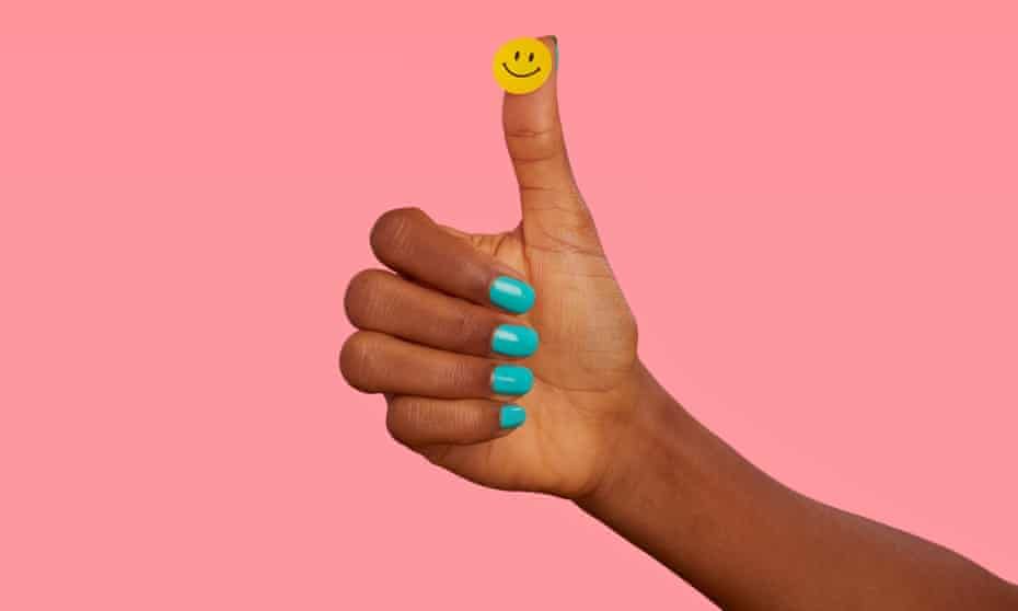 Thumbs-up hand with turquoise-painted nails and smiley sticker on thumb, against pink background