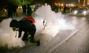 Protesters grab smoke canisters and throw them at the in Ferguson