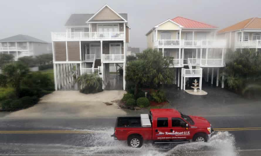 A vehicle drives through floodwaters in Ocean Isle Beach, north Carolina, on Sunday.