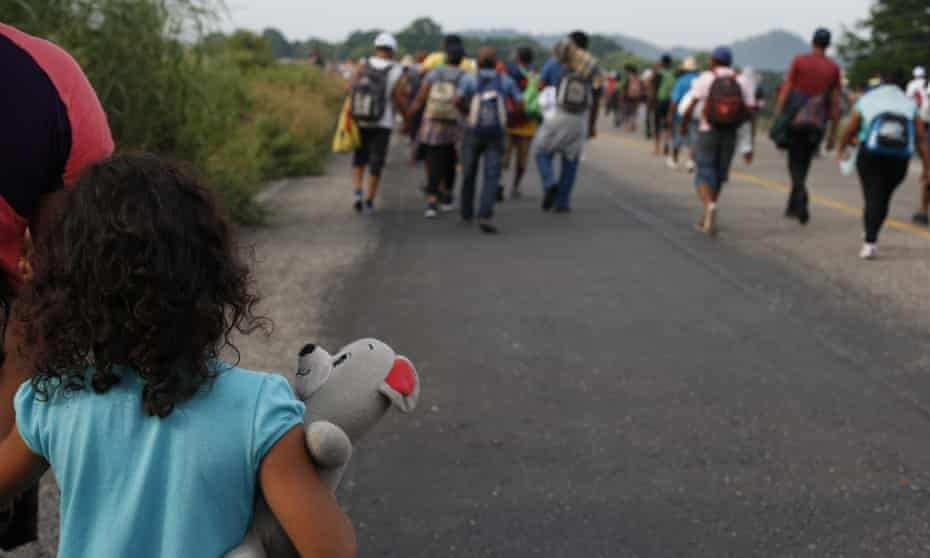 A girl carries a stuffed teddy bear as she walks with her mother near Arriaga, Chiapas state, Mexico.