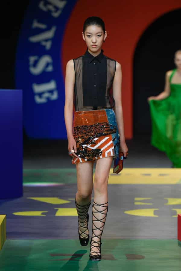 Model in a multicoloured mini skirt and black sleeveless button down shirt.