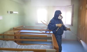 A member of a Russian radiological, chemical and biological defence unit disinfects a retirement home in Lombardy, Italy.
