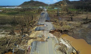 A man rides his bicycle through a damaged road in Toa Alta, west of San Juan, Puerto Rico