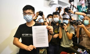 Joshua Wong holds up his notice for disqualification at a press conference in Hong Kong on 31 July.