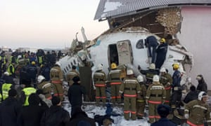 Police and rescuers work on the site of the Bek Air plane crash near Almaty International Airport, Kazakhstan
