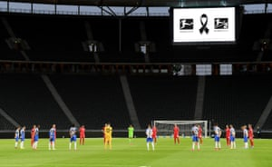 The players observe a minute's silence to commemorate the victims of the coronavirus pandemic.