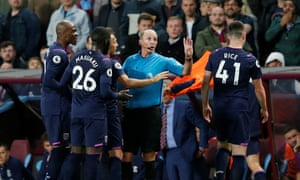 Arthur Masuaku protests his innocence after being shown a second yellow card by Mike Dean.