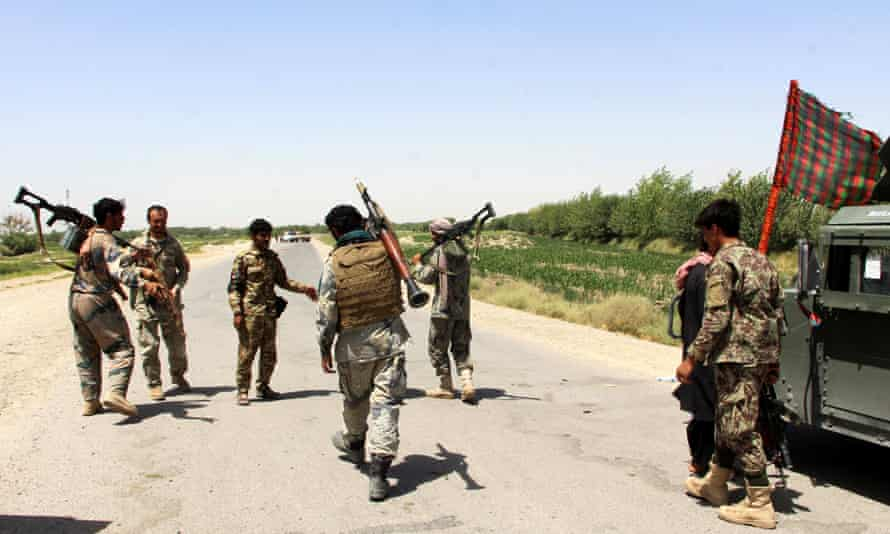 Afghan security officials patrol in Helmand province