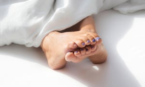 Closeup of curled feet of woman in bed with white blanket