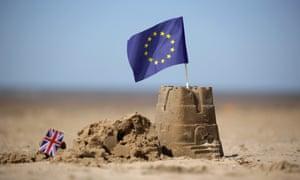 An EU flag and a union flag on sandcastles
