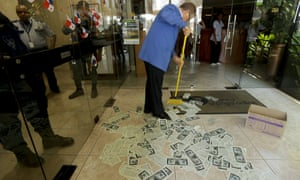 A janitor sweeps fake dollar bills placed by protesters at the entrance of the building used by the Mossack Fonseca law firm, as prosecutors raid their offices in Panama City