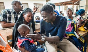 Dr Allan Pamba treats a child at Ujiji health centre, Tanzania.